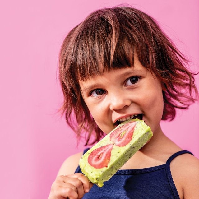 young girl eating a fancy popsicle