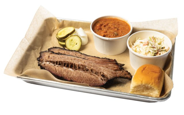 barbecue beef on a tray with beans, coleslaw, pickles and a bun