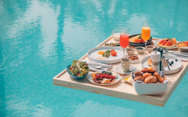 Tray of food and drinks floating in pool