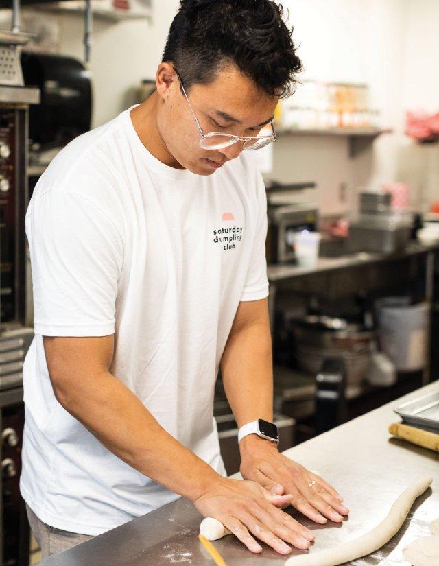 man rolling out dough