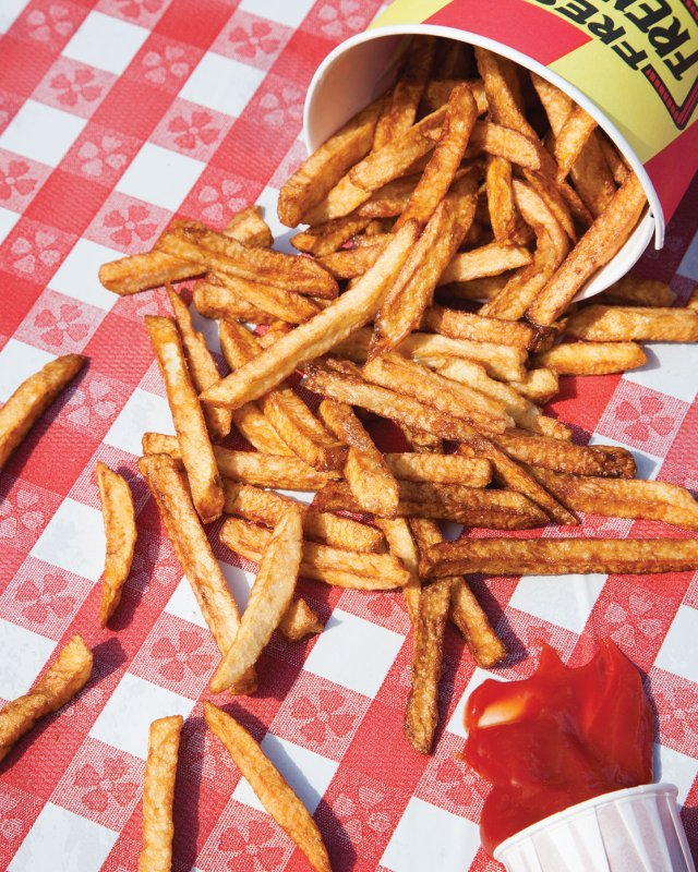 bucket of french fries spilled on table cloth