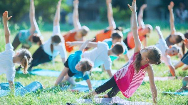 kids doing yoga outside in grass