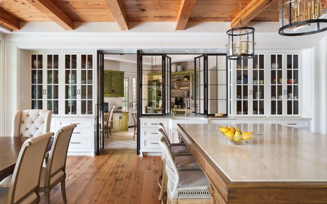 Custom steel doors and bifold windows by Minneapolis metal shop Jacobsson Carruthers connect the kitchen and garden room
