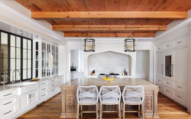 Heavy millwork, an arched range niche, and a furniture-like island create what Rauscher describes as an old European-style, grotto-like kitchen