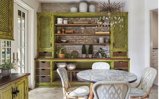 The garden room, also called the morning room, serves multiple functions: a cozy spot for coffee and breakfast, a place for potting, and a home office (with a desk on the wall opposite the potting area).