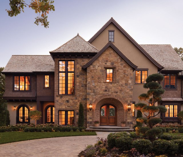 Stone, stucco, brick, and cedar-shingle siding come together to convey a Tudor style that pays homage to the site's previous structure.