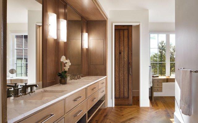 Herringbone-pattern oak flooring and white oak vanity cabinets warm up the main bath.