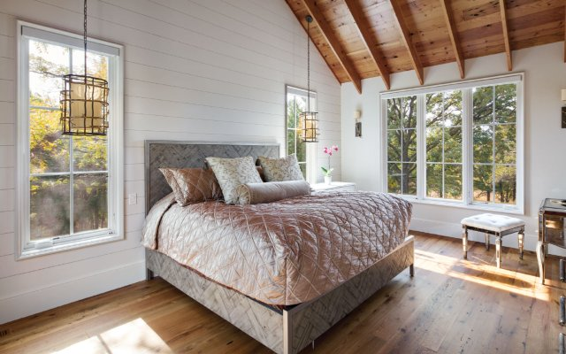 Exposed ceiling beams bring the main bedroom a lofty attic feel that makes sense given the space's upper-level perch.
