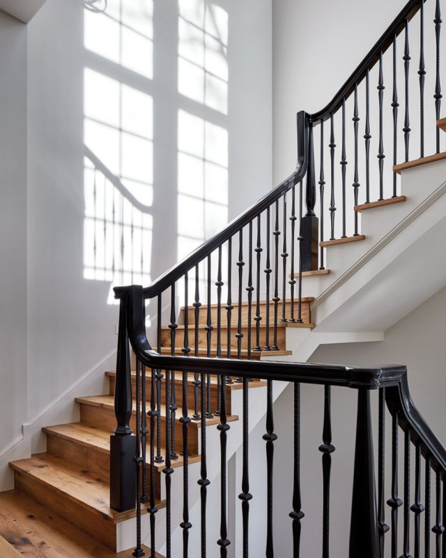 Black-lacquered wood rails and wrought-iron spindles keep the three-level stair in step with style.
