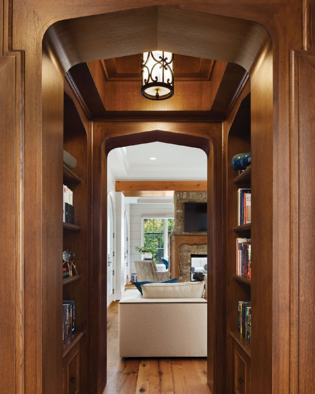 """The book-nook hallway connecting the entry foyer and library is what Rauscher calls a """"throwback to the existing house,"""" with its tight yet charming spaces."""