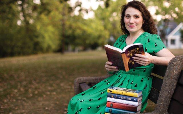 Anne Ursu reading on a park bench