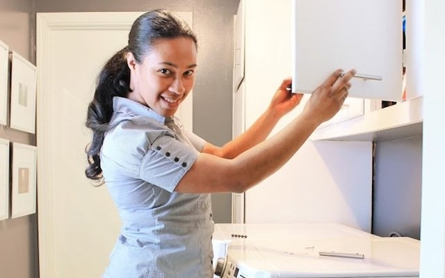 Woman opening white cabinet doors with silver hardware