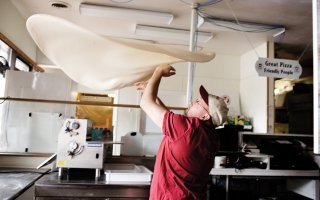 Randy Huffmeier of Randy's Premier Pizza tosses pizza dough into the air